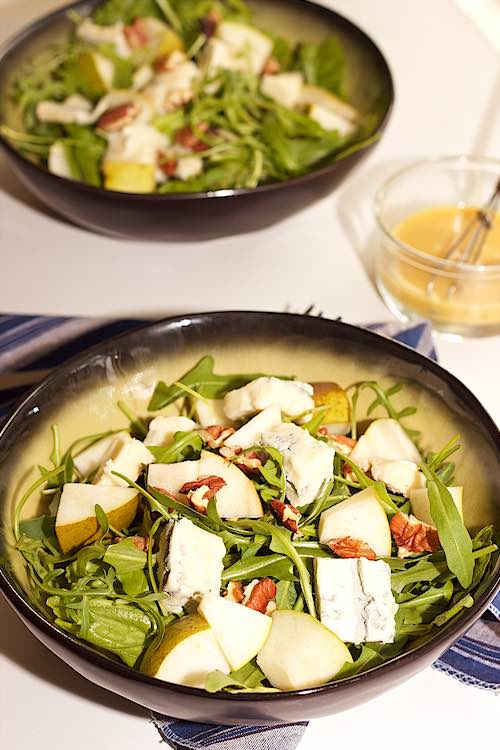 long view of 2 bowls of pear and gorgonzola salad with honey mustard dressing and pecans