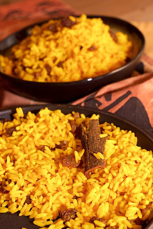 long shot of south african yellow rice with raisins and cinnamon stick in 2 bowls