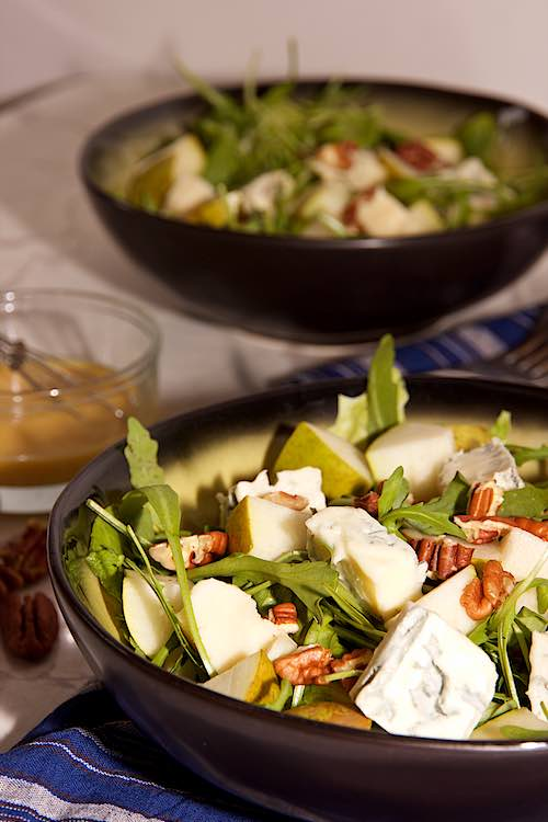 long view of 2 bowls pear salad with gorgonzola and honey mustard dressing