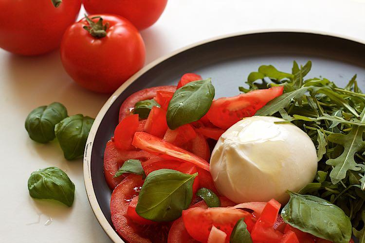 burrata salade met basilicum, rucola, tomaat op een grijs bord en witte tafel met trostomaten