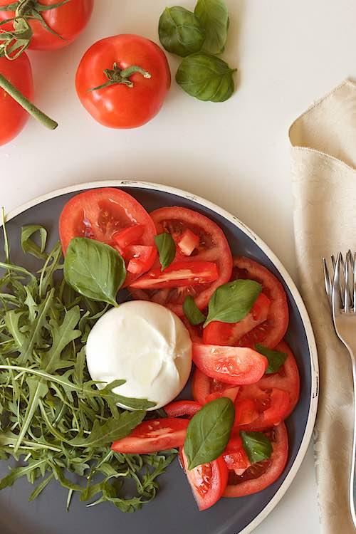bovenzicht burrata salade met tomaat, rucola en basilicum op een witte tafel, twee vorken en drie trostomaten