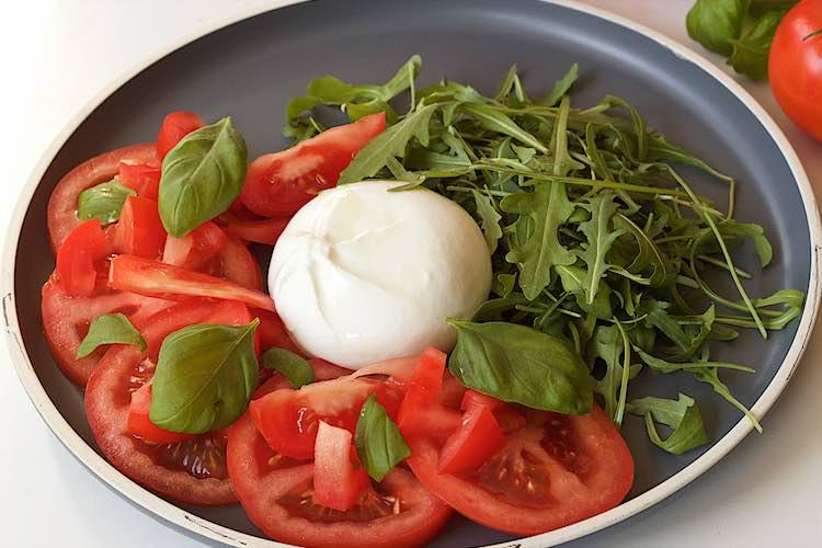 close up van burrata salade met tomaten rucola en basilicumblaadjes op een grijs bord