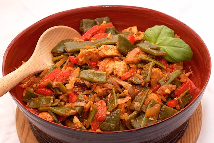 red bowl with italian green beans, red bell peppers and chicken with fresh basil leaves on a white table and wooden spoon