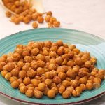 crunchy chickpeas with spices on a blue plate and a bag with chickpeas in the background on a white table