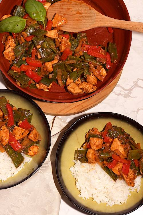bowls of rice with chicken, flat beans and bell peppers with basil leaves on a white marble table and wooden spoon