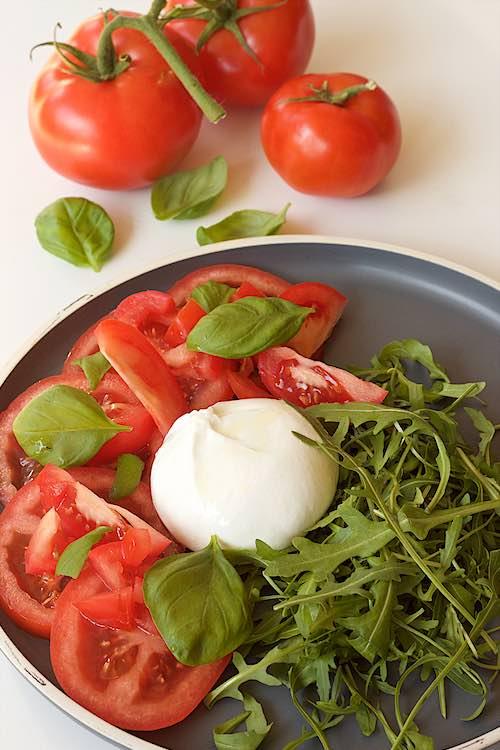 grijs bord met burrata tomaat rucola en basilicum op een witte tafel met drie trostomaten