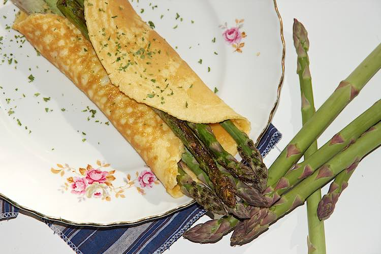 top view of omelette with asparagus grilled with parsley on a white plate with pink flowers
