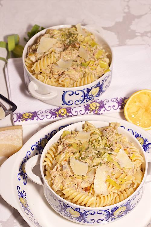 top view of two bowls of pasta with tuna and leeks with lemon, parmesan with blue flowers and a marble table