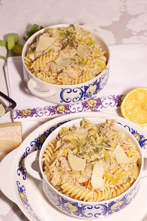 bovenaanzicht van twee kommen pasta met tonijn en prei met citroen, parmezaan schilfers op een marmeren tafel.