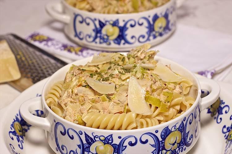 close up van romige pasta met tonijn en prei met parmezaankrullen in een witte kom met blauwe bloemen