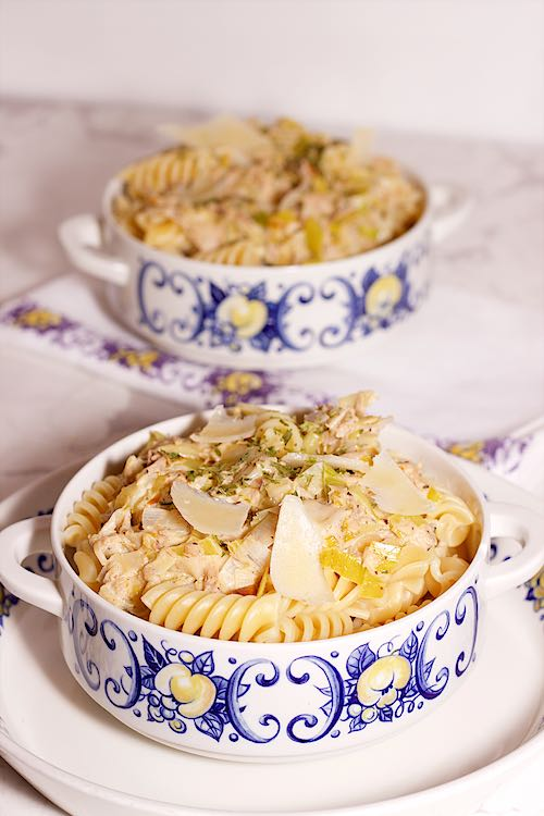 long view of two bowls of tuna pasta with leek, parmesan shavings and lemon on a white background