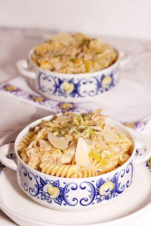 verticale foto van twee kommen pasta tonijn en prei met parmezaan en citroen op een witte marmeren tafel