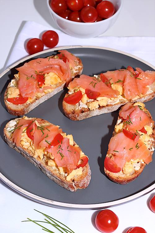 4 toast with scrambled eggs and smoked salmon on toast with cherry tomatoes and chives