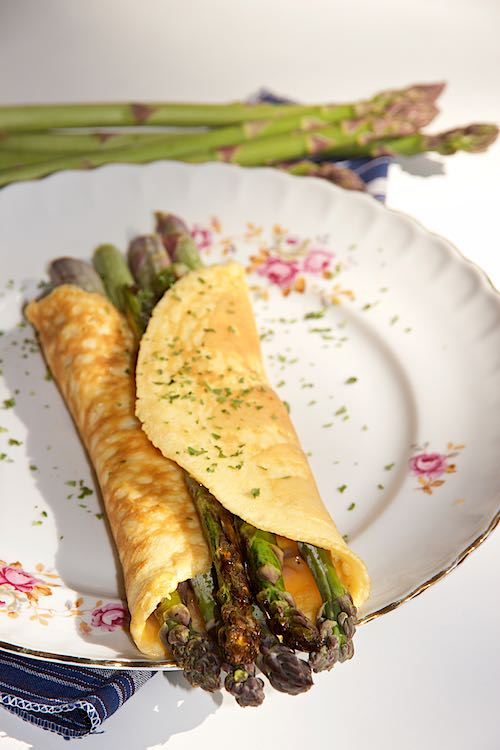 long front view of asparagus omelette on a white plate with pink flowers