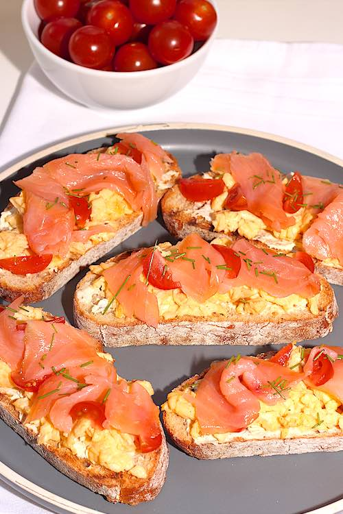 Long view of smoked salmon scrambled eggs on toast with chives and cherry tomatoes on a grey plate