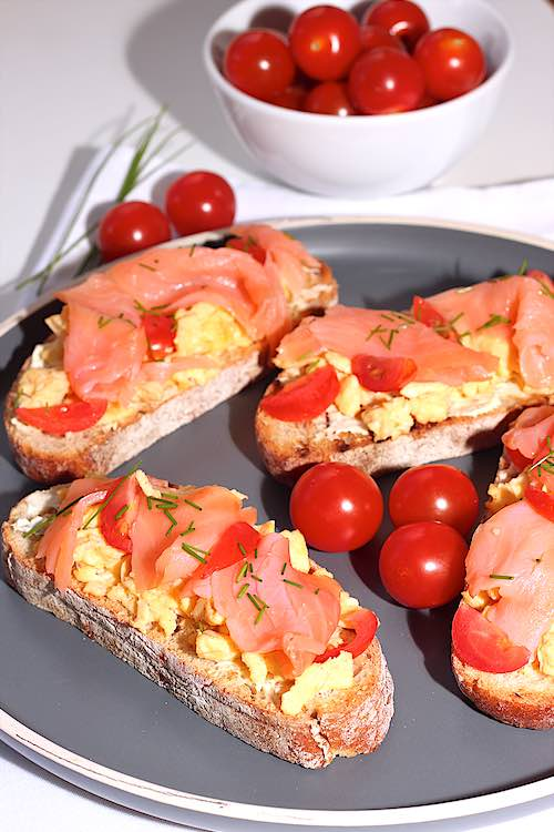 grey plate with toast of scrambled eggs smoked salmon cherry tomatoes and chives
