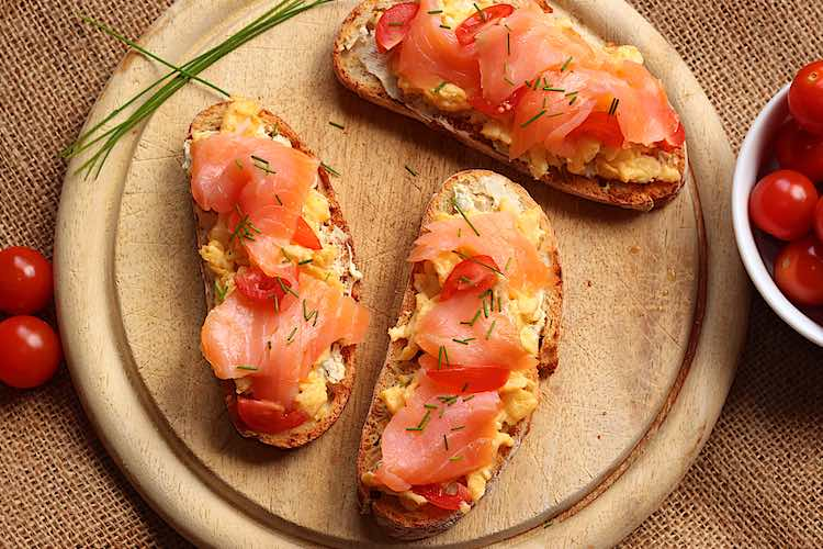 wooden board with 3 toast smoked salmon scrambled eggs cream cheese chives cherry tomoatoes