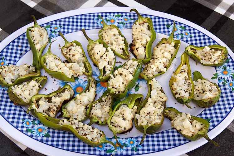 Pimientos de padron gevuld met feta kaas op een blauw geruit bord
