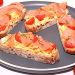 clove up of scrambled egg with smoked salmon on toast on a grey plate with cherry tomatoes