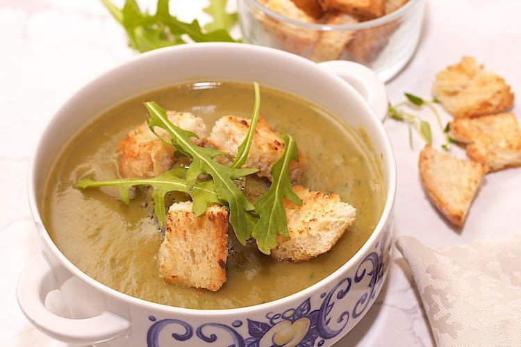 close up courgette soep met rucola en croutons in een witte kom
