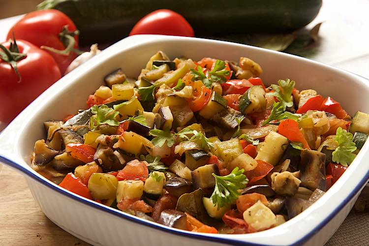 close up of french ratatouille in a white dish with summer vegetables