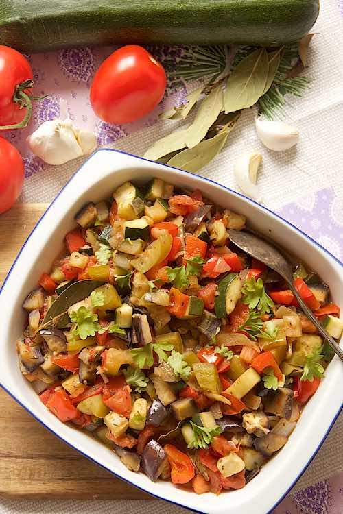 top long view of a dish with ratatouille with tomato, zucchini, bay leaf, garlic