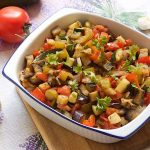 top close up of ratatouille in a white dish with garlic and tomatoes