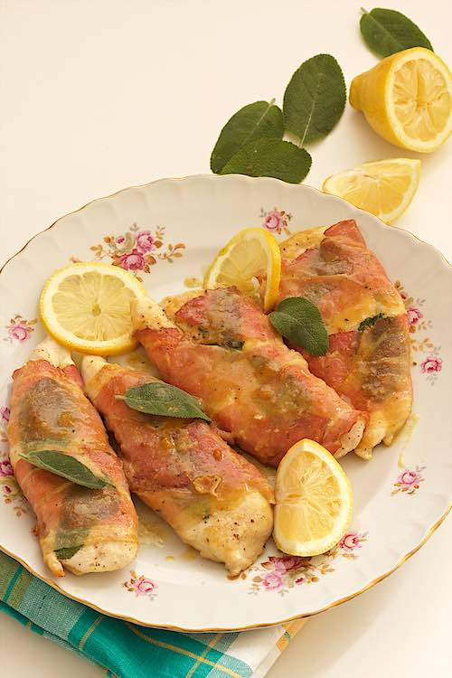 4 saltimbocca chicken with sage, prosciutto and lemon on a white and pink plate