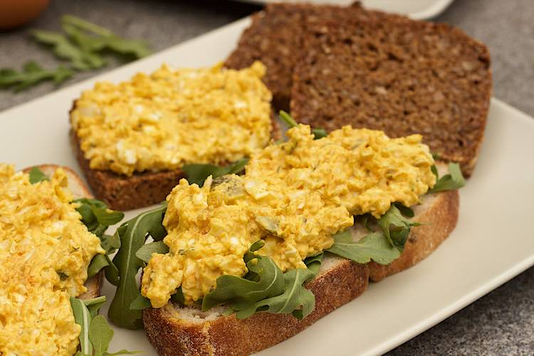 close up sneetjes brood met eiersla en rucola op een wit rechthoekig bord