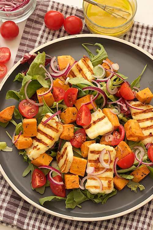 bovenzicht van een grijs bord met zoete aardappel salade en gegrilde halloumi met kerstomaten, rode ui en tahin dressing