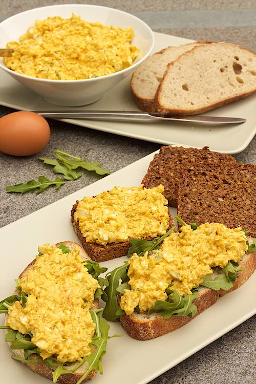 vertikale foto van eiersalade met rucola op brood of eiersla met curry