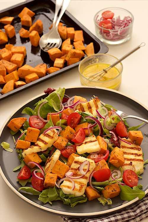 verticale foto van salade met zoete aardappel en halloumi met tahini dressing