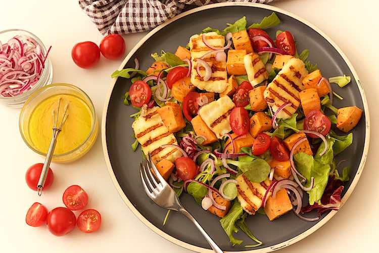 bovenzicht van gegrilde halloumi salade met zoete aardappel en tahini mosterd dressing rode ui en kerstomaten