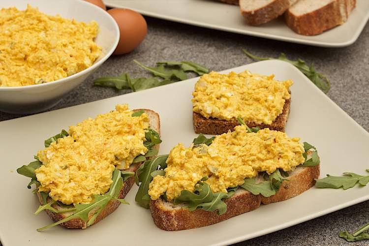 vooraanzicht van 3 sneden brood met zelfgemaakte eiersla en rucola