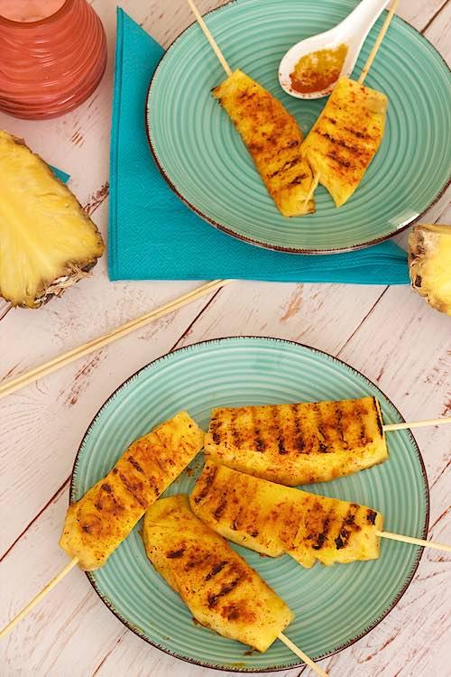 verticale zicht van pittige gegrilde ananas spiesjes op een blauwe bord met witte houten tafel