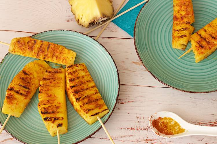 ananas spiesjes met curry en chili op een blauw bord