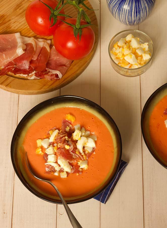 bovenzicht salmorejo spaanse koude tomatensoep met ham en hardgekookte eieren op een witte houten tafel