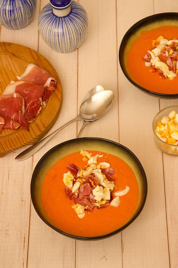 top zicht twee kommen spaanse salmorejo soep met spaanse ham, hardgekookt ei en tomaten op een witte houden tafel