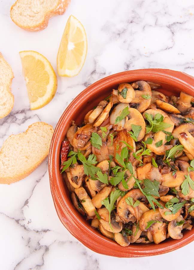 bovenzicht spaanse knoflook champignons met stokbrood en citroen schijfjes