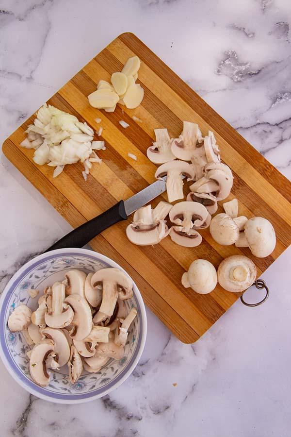 champignons, ui en knoflook snijden