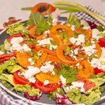 close up van gegrilde kakisalade met feta, tomaat, lente-ui en pecannoten op een witte tafel