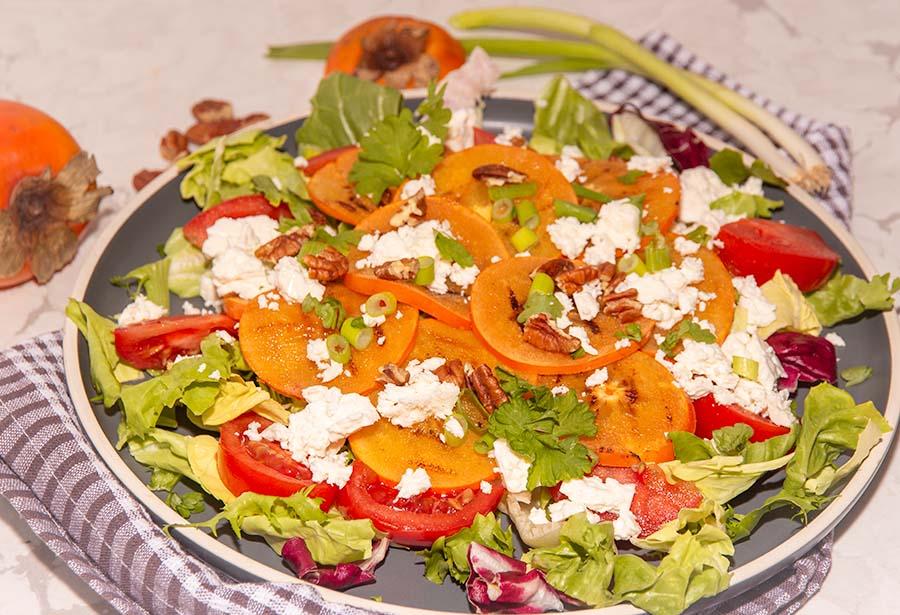 close up van salade met kaki of persimmon met feta kaas, tomaat en gemengde sla