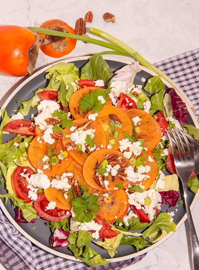 bovenzicht kakisalade met tomaat fetakaas lente-ui en een mosterd tahini dressing
