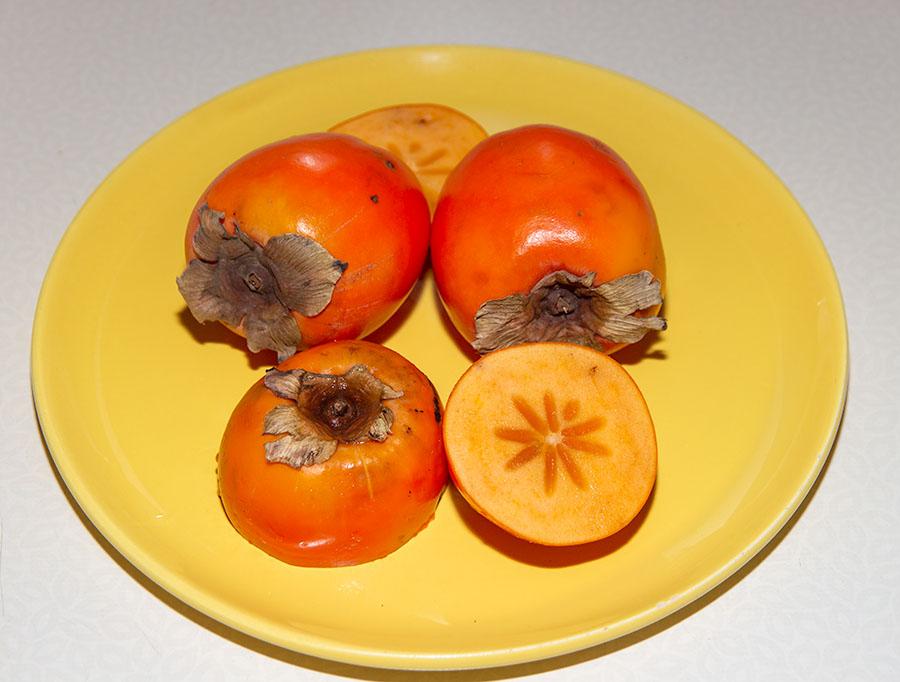 drie kaki vruchten op een geel bord doormidden gesneden
