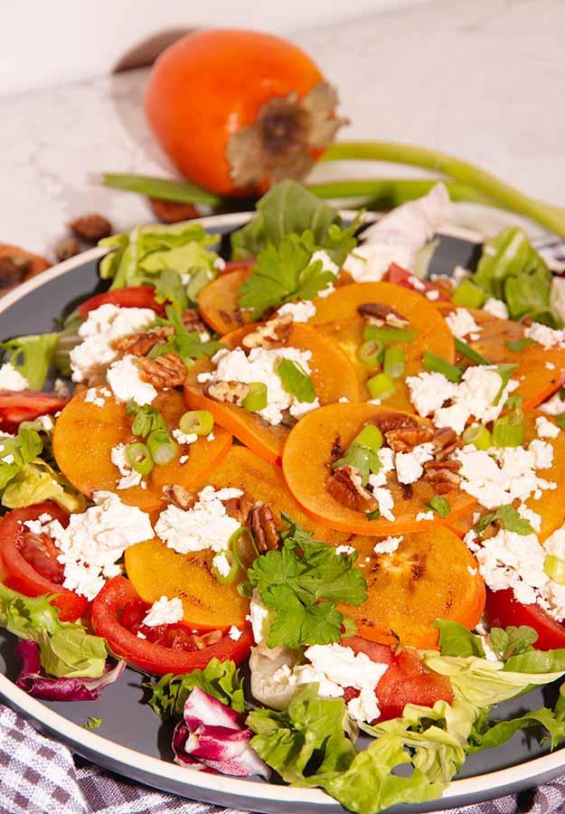 verticale foto gegrilde kakisalade met feta, sla, tomaat op een grijs bord