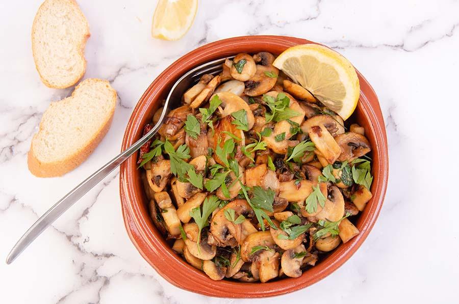 bovenzicht champignons met knoflook met een schijfje citroen en stokbrood en peterselie